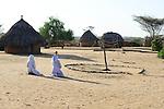 KENYA Turkana, Lodwar, two christian Turkana women pray in openair church in village / KENIA, Turkana, Lodwar, zwei christliche Turkana Frauen beten in Kirche unter freiem Himmel