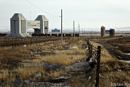 A train carrying Russian timber passes the border from Russia to China (from the town of Zabaikalsk to Manzhouli), bringing wood to the resource-hungry Asian giant. The big grey gate belongs to China, while the smaller one belongs to Russia, reflecting the economic and power shift of the two giant nations.