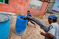 A Peruvian water distribution worker with a pipe fills a plastic barrel with drinking water on the dusty hillside of Pachacútec, a desert suburb of Lima, Peru, 21 January 2015. Although Latin America (as a whole) is blessed with an abundance of fresh water, having 20% of global water resources in the the Amazon Basin and the highest annual rainfall of any region in the world, an estimated 50-70 million Latin Americans (one-tenth of the continent's population) lack access to safe water and 100 million people have no access to any safe sanitation. Complicated geographical conditions (mainly on the Pacific coast), unregulated industrialization (causing environmental pollution) and massive urban poverty, combined with deep social inequality, have caused a severe water supply shortage in many Latin American regions.