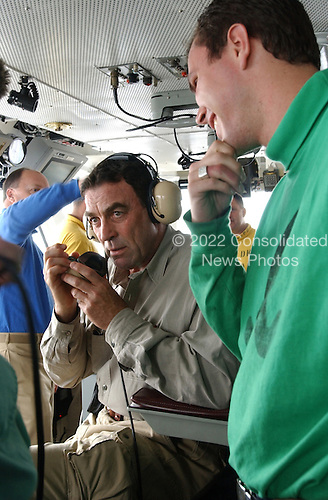 Aviation Boatswain's Mate Kevin Maguire instructs actor Tom Selleck on the function of the ship's sound-powered telephone system on July 22, 2004. Mr. Selleck used the system to speak with crew members in the below deck arresting gear rooms from the ship's bridge aboard USS Ronald Reagan's (CVN 76). Tom Selleck was aboard Reagan to welcome the ship's crew to Naval Air Station North Island, San Diego, California. Homeporting ceremonies for the Navy's newest and most technologically advanced aircraft carrier will host various dignitaries, including Nancy Reagan, members of the Congress, state officials and various celebrities. Reagan is commanded by Captain James A. Symonds. While in transit, the ship visited the ports of Rio de Janeiro, Brazil, Valparaiso, Chile, and Callao, Peru. <br /> Mandatory Credit: Stefanie Broughton / USN via CNP