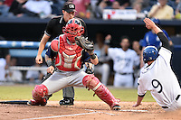 Hagerstown Suns catcher Matt Reistetter (11) fields the ball and attempts to tag out a hard sliding Eric Toole (9) during a game against the  Asheville Tourists at McCormick Field on September 4, 2016 in Asheville, North Carolina. The Suns defeated the Tourists 10-5. (Tony Farlow/Four Seam Images)