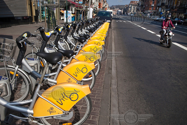 A row of bicycles parked in a dock. In order to promote the use of bicycles in the city 180 such Villo stations have been opened, one every 450 metres.