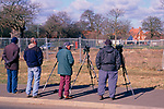 A753WD Four male birdwatchers with binoculars mounted on tripods looking towards waste ground