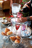 Champagne being poured into coloured glasses to be served together with pastries for an aperitif on Christmas day