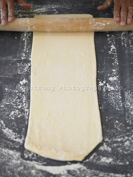 Rolling out croissant dough on a floured surface.