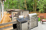 A built in stainless steel gas grill and refrigerator with a granite slab worktop sit beside a large wooden deck set for outdoor entertaining with flowers, condiments, wine, and a bucket of cold drinks, all of which backs to a greenspace of Northwest native evergreens and ferns in this devlopment about an hour from Seattle.