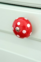 The kitchen cupboards are decorated with cheerful red knobs with white polka dots