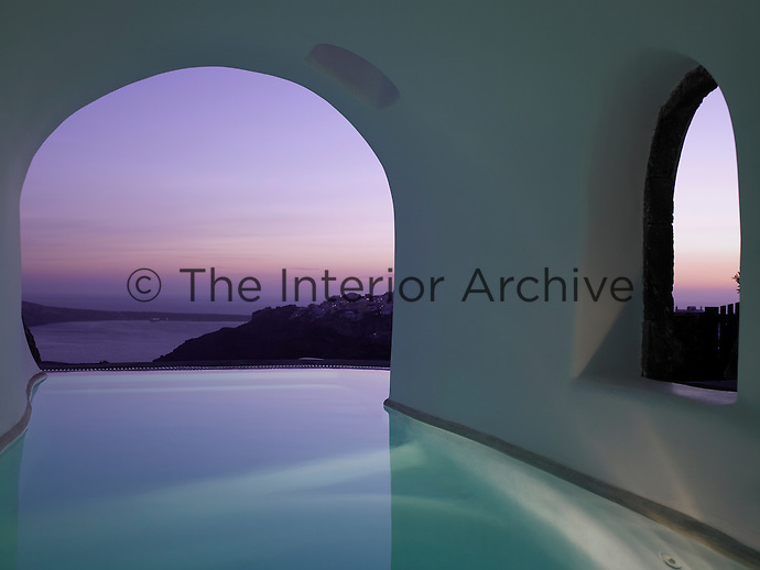 The infinity pool of the Perivolas Hotel in Santorini has a stunning setting under a series of arches with panoramic views of the Mediterranean beyond