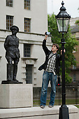 A man videos a protest march in Whitehall, next to a stature of Field Marshall the Viscount Alanbrooke.