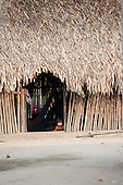 Aldeia Baú, Para State, Brazil. baby in the doorway of a thatched house.