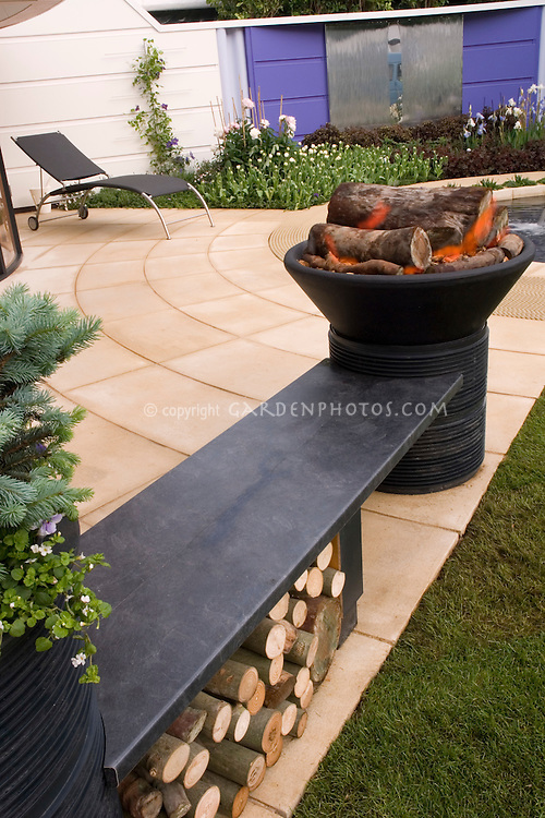 Outdoor backyard fireplace firepit with fire on patio