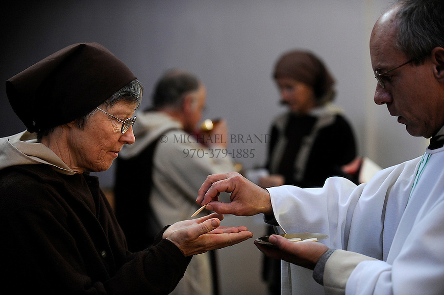Patricial McGowan receives communion from Eric Haarer during noon mass at the Nada Carmelite Hermitage in Crestone, CO. Michael Brands for The New York Times.