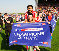Lincoln City's Bruno Andrade jumps on the back of Tom Pett to celebrate securing the League 2 Title<br /> <br /> Photographer Andrew Vaughan/CameraSport<br /> <br /> The EFL Sky Bet League Two - Lincoln City v Tranmere Rovers - Monday 22nd April 2019 - Sincil Bank - Lincoln<br /> <br /> World Copyright © 2019 CameraSport. All rights reserved. 43 Linden Ave. Countesthorpe. Leicester. England. LE8 5PG - Tel: +44 (0) 116 277 4147 - admin@camerasport.com - www.camerasport.com