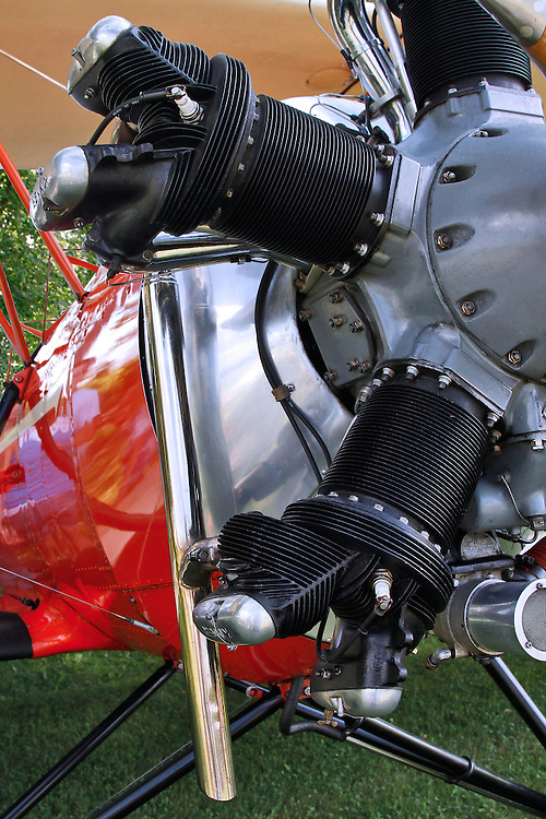 Close uo of a silver Kinner Radial Engine on a red and silver Meyers OTW (out-to-win) highlighting two of the five cylinders and a chrome exahust. Photograph taken at the 2010 Wings 'n' Wheels Showcase.