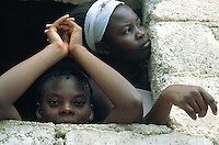 Haiti. Province of Ouest. Port-Au-Prince. Slum of Campeche. Densely populated area. Houses where families live in. Two young girls look out of their window. © 2003 Didier Ruef
