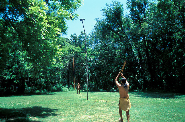 Two traditionally dressed Cherokee men demonstrate how a stickball game would be played in Tahlequah OK at the Indian Village.