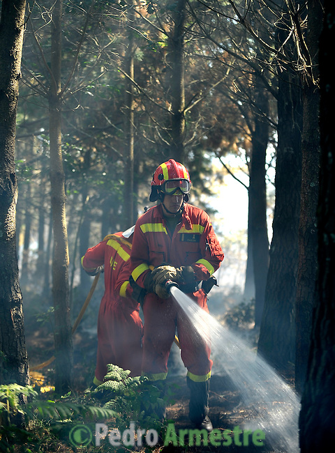 A member of the Spanish Army Emergency Unit (UME) works around the fire area in Boiro, on August 16, 2010, near A Coruna.  Pedro ARMESTRE