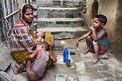 Maina Devi breastfeeds her 3 month old daughter, Priya and her other two children, Pawan Kumar (4, right) and Pradeep (2, left) sit next to her in the courtyard of their hut in Bhelaiya village in Raxaul, Bihar, India.