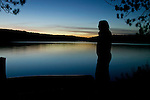 A woman watches dusk settle on Galerairy Lake during sunset at Ontario's Algonquin Provincial Park in Canada.