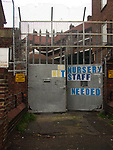 A51P83 Nursery staff needed poster on metal doors with security fencing and wire London England