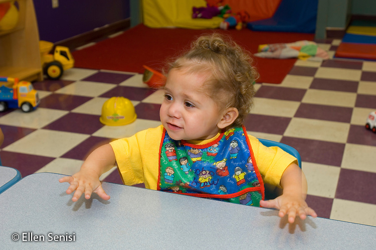 MR / Schenectady, NY.Schenectady Day Nursery / private non-profit daycare center / Toddler class.Toddler (girl, 1, African-American / Caucasian) slapping her hands on a table..MR: War10.© Ellen B. Senisi