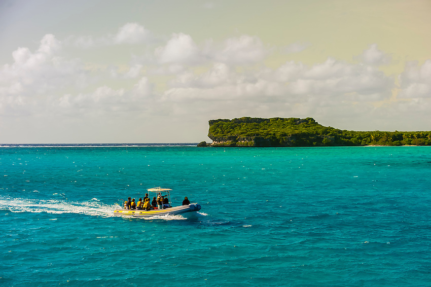 A zodiac carrying tourists with Fayawa Island in background, part of the Island of Ouvea, Loyalty Islands, New Caledonia