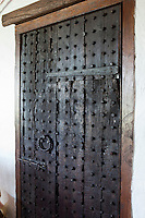 A heavy wooden door studded with iron nails