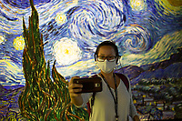 """LISBON, PORTUGAL - MAY 31: A visitor takes a selfie with a cellphone at the """"Meet VicentVanGogh"""" exhibition as the spread of the (COVID-19) continues in Lisbon, on May 31, 2020. Meet Vincent van Gogh is an interactive experience, to get to know Lisbon, through which it proposes to make Vincent's art accessible to as many people as possible.<br /> (Photo by Luis Boza/VIEWpress via Getty Images)"""