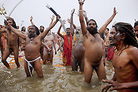 "India. Uttar Pradesh state. Allahabad. Maha Kumbh Mela. Royal bath on Basant Panchami Snan (fifth day of the new moon). The ritual ""Royal Bath"" is timed to match an auspicious planetary alignment, when believers say spiritual energy flows to earth. Naga (naked) Sadhus celebrate their joy by taking a dip at Sangam and worshiping the river Ganges. A few Naga Sadhus have their bodies smeared with ashes. They were once warriors, that's why they still carry weapons, such as Trishula with Dumroo and Sword. A trishula is a type of Indian trident, commonly used as a Hindu religious symbol. The word means ""three spear"" in Sanskrit. The trishula is wielded by the Hindu God Shiva. The sword is the weapon of Kali who is the Hindu goddess associated with empowerment. The Kumbh Mela, believed to be the largest religious gathering is held every 12 years on the banks of the 'Sangam'- the confluence of the holy rivers Ganga, Yamuna and the mythical Saraswati. In 2013, it is estimated that nearly 80 million devotees took a bath in the water of the holy river Ganges. The belief is that bathing and taking a holy dip will wash and free one from all the past sins, get salvation and paves the way for Moksha (meaning liberation from the cycle of Life, Death and Rebirth). Bathing in the holy waters of Ganga is believed to be most auspicious at the time of Kumbh Mela, because the water is charged with positive healing effects and enhanced with electromagnetic radiations of the Sun, Moon and Jupiter. In Hinduism, Sadhu (good; good man, holy man) denotes an ascetic, wandering monk. Sadhus are sanyasi, or renunciates, who have left behind all material attachments. They are renouncers who have chosen to live a life apart from or on the edges of society in order to focus on their own spiritual practice. The significance of nakedness is that they will not have any worldly ties to material belongings, even something as simple as clothes. 15.02.13 © 2013 Didier Ruef"