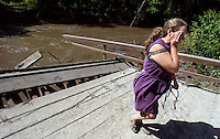 "Julie Bowers, executive director of the North Skunk River Greenbelt Association, wipes away tears as she walks away from the edge of the destroyed McIntyre Bridge on the North Skunk River at the Millgrove Access Wildlife Area in southwest Poweshiek County, August 15, 2010.  Bowers had been leading an effort to restore the bridge.  The bridge, a bowstring truss, was built in 1883 by the King Iron Bridge Company of Cleveland, Ohio, and is considered one of the rarest and most historically significant types of bridges in the country.  Damaged by an ice jam in 2009, and flooding this summer, it finally gave way to nature after spanning the river for 127 years.  ""I never expected to not see those arches,"" she said weeping.  ""But it shocked me today when the bridge wasn't there."""