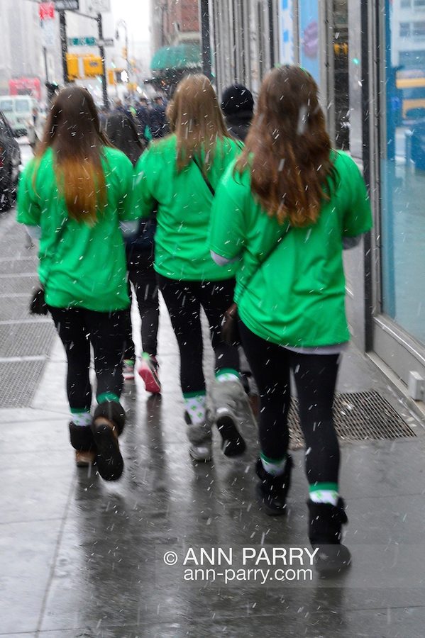 March 16, 2013 - New York, NY, U.S. - Though it snowed during the 252nd annual NYC St. Patrick's Day Parade, thousands of marchers showed their Irish pride, as they marched up Fifth Avenue, and over a million watched and celebrated. These girls are walking a short distance away from the end of the parade route.