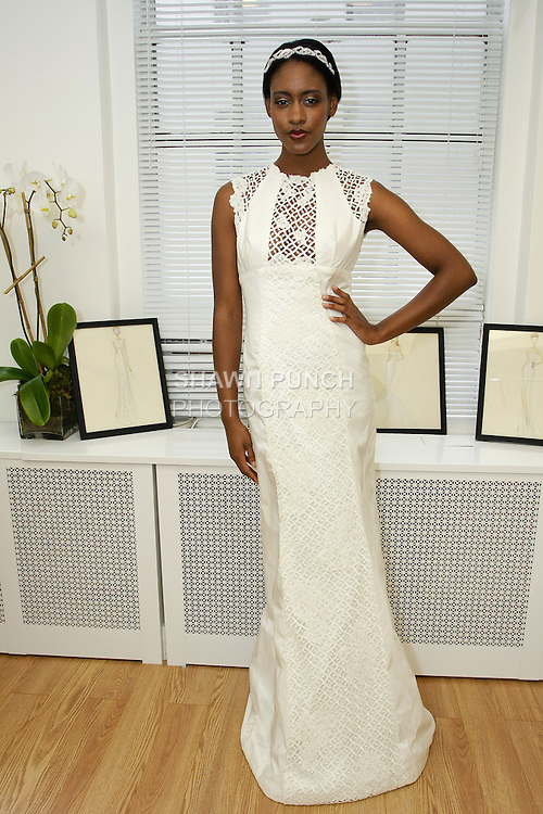 "Model poses in ""Cilo"" - a cap sleeve taffeta gown with guipure lace insets, from the Sarah Jassir Fall 2013: From Concept To Creation collection, for her Angelique Bridal store opening at 6 East 45 Street, during New York Bridal Fashion Week, October 15, 2012"