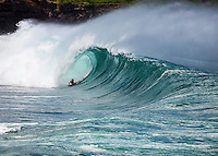Body boarder getting barreled on a large wave at Waimea Bay Shorbreak, North Shore, Oahu