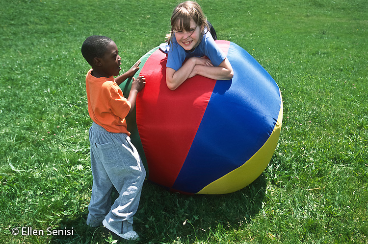MR / Schenectady, NY. Yates Arts in Education Magnet Elementary School. Friends play with big ball (activity ball from gym class) on grass. Left: boy, 4, African-American, pre-k; right: girl, 6, grade 2. MR: Far2, Koe2. ID: AJ-LC. © Ellen B. Senisi