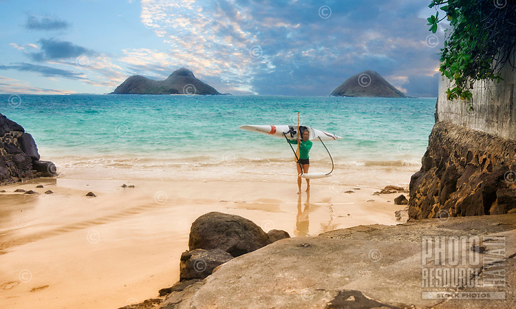 A solo outrigger canoe paddler carries her canoe onto a secluded section of Lanikai Beach, O'ahu, with the Mokulua Islands in the distance.