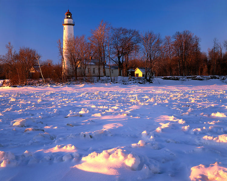 Winter sunrise light on Pointe Aux Barques Lighthouse on Lake Huron; Huron County, Michigan