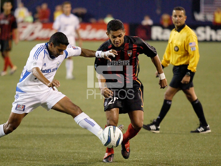 The  Wizard's Diego Gutierrez tackles the ball away from the MetroStars' Amado Guevara as  referee Hector Tobon looks on. The Kansas City Wizards were defeated by  the NY/NJ MetroStars to a 1 to 0 at Giant's Stadium, East Rutherford, NJ, on May 30, 2004.