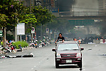 16 MAY 2010 - BANGKOK, THAILAND: People in a pick up truck flee fighting on Rama IV Road in Bangkok Sunday. Thai troops and anti government protesters clashed on Rama IV Road again Sunday afternoon in a series of running battles. Troops fired into the air and unidentified snipers shot at pedestrians on the sidewalks. At one point Sunday the government said it was going to impose a curfew only to rescind the announcement hours later. The situation in Bangkok continues to deteriorate as protests spread beyond the area of the Red Shirts stage at Ratchaprasong Intersection. Many protests now involve people who have not been active in the Red Shirt protests and live in the vicinity of Khlong Toei slum and Rama IV Road. Red Shirt leaders have called for a cease fire, but the government indicated that it is going to go ahead with operations to isolate the Red Shirt camp and clear the streets.      PHOTO BY JACK KURTZ