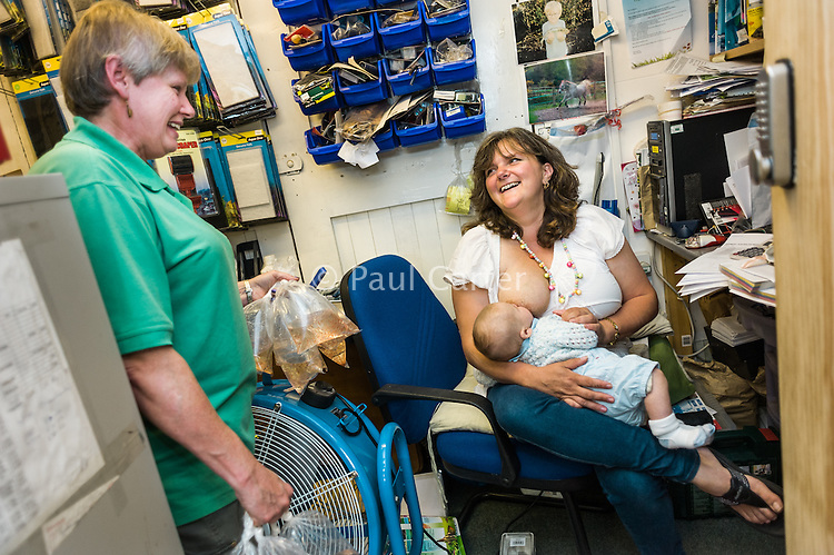 A woman breastfeeding her baby boy at work in her shop's office.<br /> <br /> 11 August 2011<br /> Dorset, England, UK