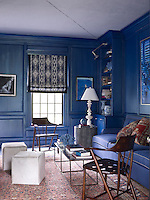 A pair of vintage webbed-leather armchairs flanks the coffee table in the library which has been painted an indigo blue