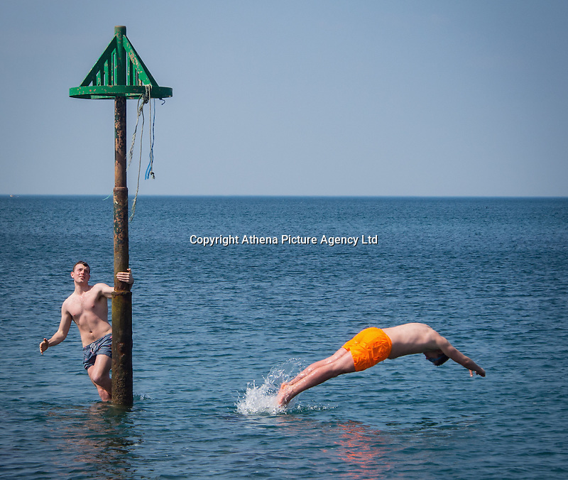 UK Weather: Aberystwyth, Ceredigion, West Wales Thursday 12th May 2016. <br /> Two young men take a plunge off the end of the wooden jetty