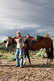 USA, Wyoming, Encampment, a woman stands and smiles next to her horse on a mountain top, Abara Ranch