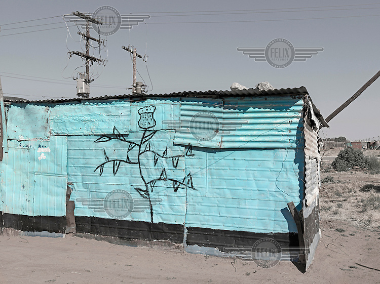 A corrugated iron shack neatly painted with blue paint and a picture of a thistle. Graeme Williams' pictures of the environments occupied by some of South Africa's poorest people focus on the interiors and exteriors of people's homes, accentuating the minutiae of the occupants' day-to-day dwelling places. The bright colours captured in these photographs are suggestive of resilience, hope and a sense of humanity that survives in these poverty-stricken communities...