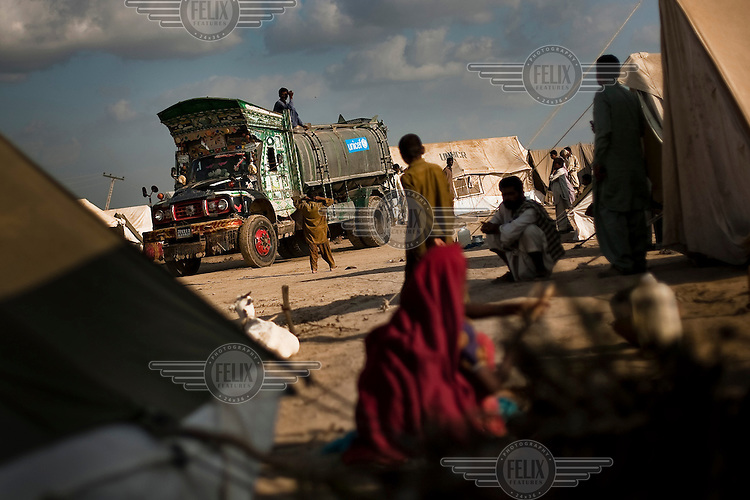 People displaced by flooding watch the arrival of a UNICEF water tanker at a relief camp.