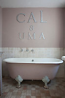 Silver letters mounted on the wall above the roll top bath, all painted in a dusky pink