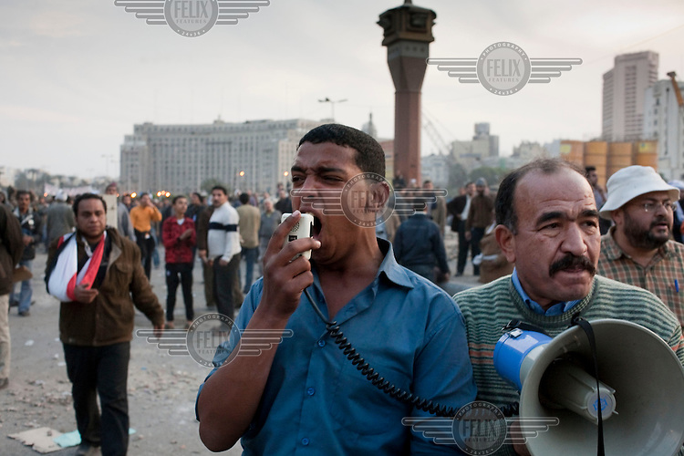 A young man cries out 'God is Great' over a megaphone in the midst of violent clashes between protesters and supporters in Tahrir Square. Continued anti-government protests take place in Cairo calling for President Mubarak to stand down. After dissolving the government, Mubarak still refuses to step down from power.