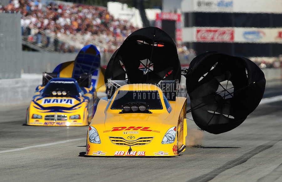 Nov 13, 2010; Pomona, CA, USA; NHRA funny car driver Jeff Arend (right) races alongside Ron Capps during qualifying for the Auto Club Finals at Auto Club Raceway at Pomona. Mandatory Credit: Mark J. Rebilas-