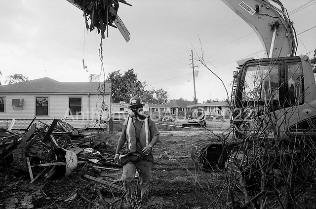 Saint Bernard's Parish, Louisiana.May 26, 2006..Demolition teams work at leveling as many as 6,000+ homes in St. Bernard's Parish damaged by hurricane Katrina in August of 2005...FEMA is offering to destroy home for free up until June 30, 2006. About 12 homes are being demolished a day (so far). ..Workers are outfitted in special clothing and masks and water is poured on to the debris as the homes have asepses. The water is to keep down the asepses fumes.