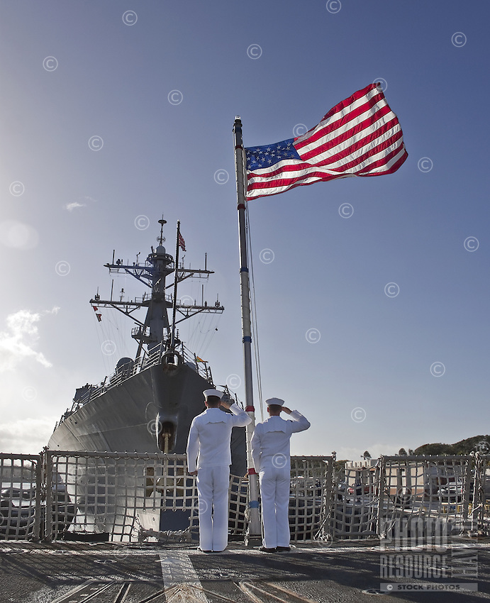 Two US Navy sailors saluting the flag during the Morning Colors ceremony on board USS Chung-Hoon (DDG 93) at Pearl Harbor on Oahu, Hawaii. .