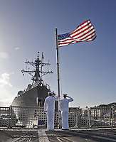 Two US Navy sailors saluting the flag during the Morning Colors ceremony on board USS Chung-Hoon (DDG 93) at Pearl Harboron Oahu, Hawaii..